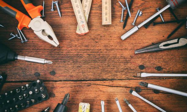 vielzahl von handwerkzeugen auf einem holztisch - werkzeugbank stock-fotos und bilder