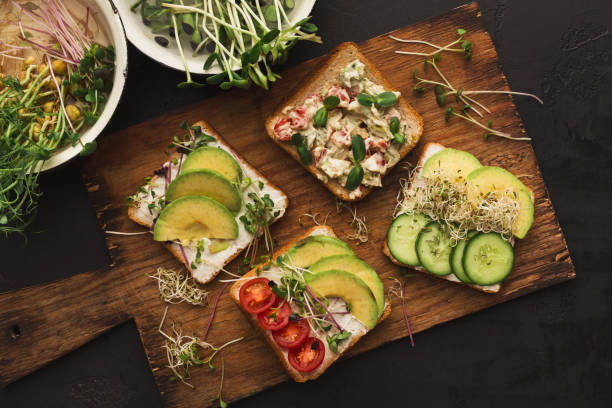 Variety of healthy vegetarian sandwiches Vegetarian wholegrain sandwiches with micro greens. Vegan party food table with organic vegetables canapes. Healthy lifestyle and eating right concept microgreen stock pictures, royalty-free photos & images