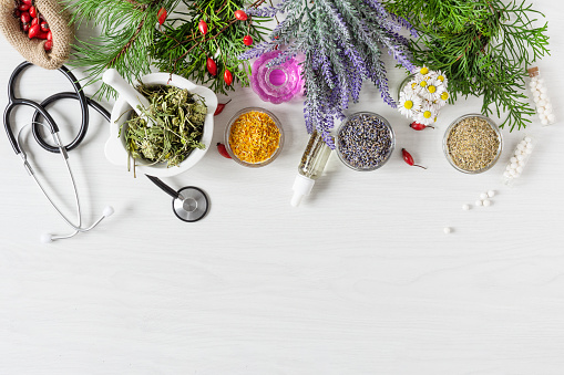 Variety of herbs and herbal mixtures as an alternative medicine concept on wooden table background top view. Homeopathy treatment.