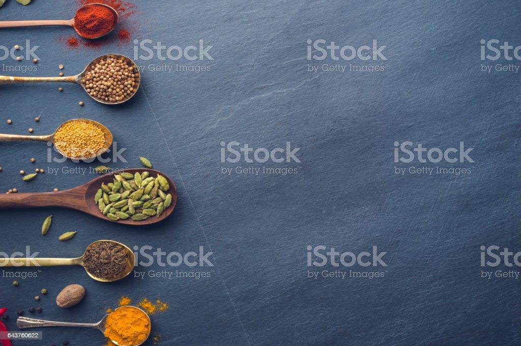 Variété d'herbes et d'épices sur fond ardoise. - Photo