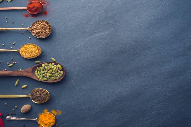 variedad de hierbas y especias en fondo de pizarra. - comida india fotografías e imágenes de stock