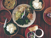 Variety of local vegetables having with curry rice noodle and mixed many kind of sauce for Thai rice noodle on wooden table famous food of Thailand. - A set of Thai cuisine. (Thai northern style).