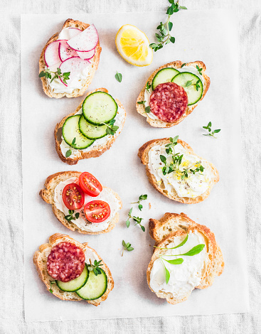 istock Variety of mini sandwiches with cream cheese, vegetables and salami. Sandwiches with cheese, cucumber, radish, tomatoes, salami, thyme, lemon zest on a light background, top view. Flat lay 670881016