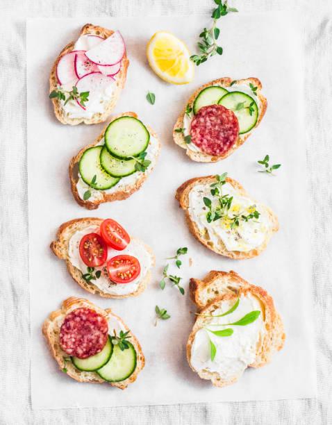 auswahl an mini-sandwiches mit frischkäse, gemüse und salami. brötchen mit käse, gurken, rettich, tomaten, salami, thymian, geriebene zitronenschale auf einem hellen hintergrund, ansicht von oben. flach zu legen - salami vorspeise stock-fotos und bilder