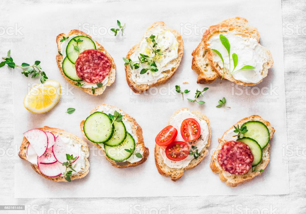 Variety of mini sandwiches with cream cheese, vegetables and salami. Sandwiches with cheese, cucumber, radish, tomatoes, salami, thyme, lemon zest on a light background, top view. Flat lay stock photo