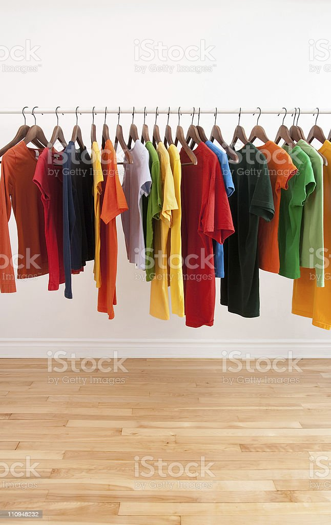 Variety of multicolored clothes on a rod stock photo