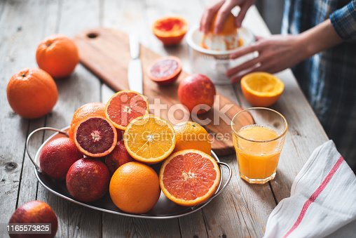 Whole and halved a variety of oranges on a metal tray on a gray wooden table, in the background a girl squeezes juice from oranges