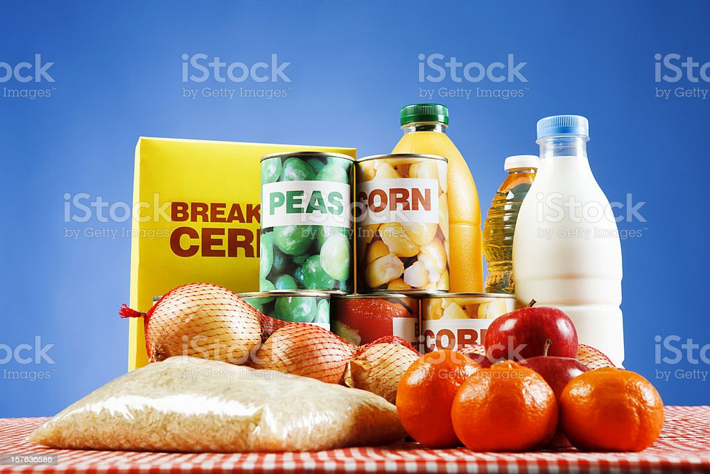Variety of packaged and basic foods against blue stock photo