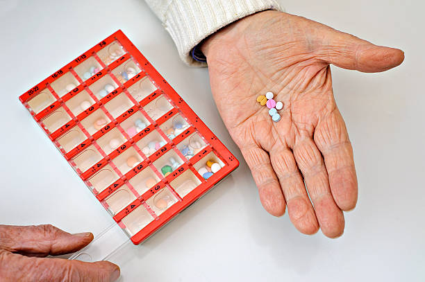 Variety of pills in an elderly hand stock photo