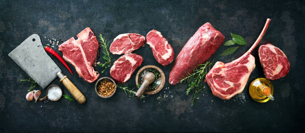 Variety of raw beef meat steaks for grilling with seasoning and utensils stock photo