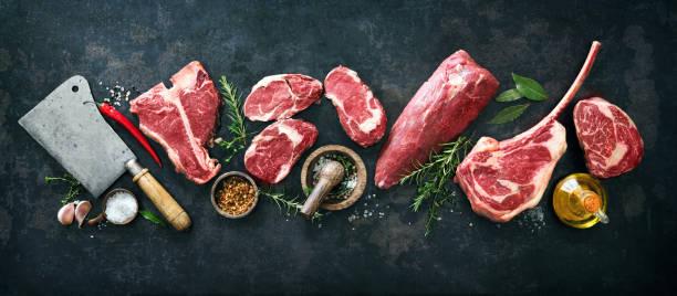 vielzahl von rohen rindfleisch-fleischsteaks zum grillen mit gewürzen und utensilien - fleisch stock-fotos und bilder