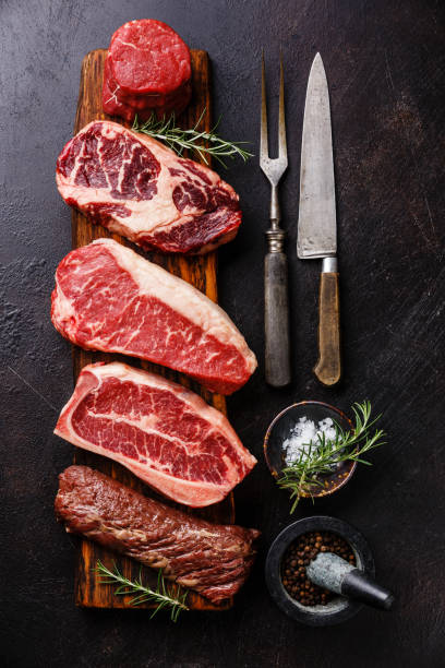 variety of raw black angus prime meat steaks and seasoning - meat stock photos and pictures