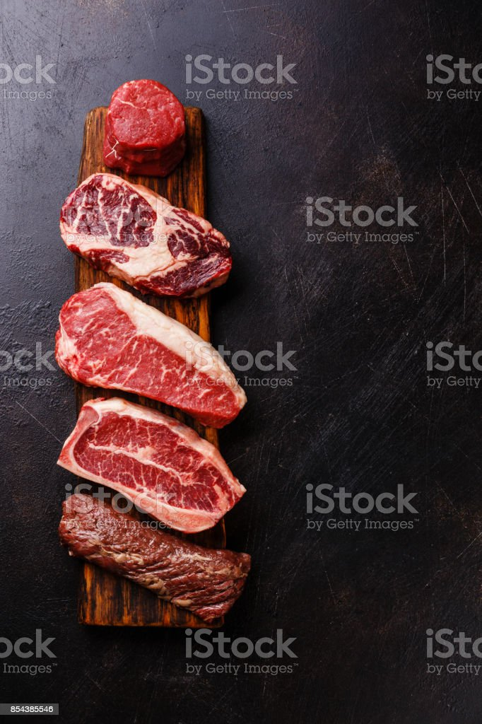 Variety of Raw Black Angus Prime meat steaks Machete, Blade on bone, Striploin, Rib eye, Tenderloin fillet mignon stock photo