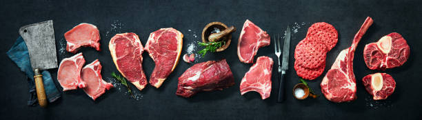 Variety of raw cuts of meat, dry aged beef steaks and hamburger patties stock photo