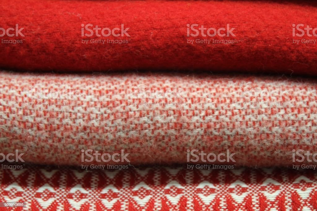 variety of red toned blankets folded