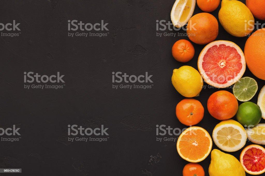 Variety of ripe citruses on black background zbiór zdjęć royalty-free