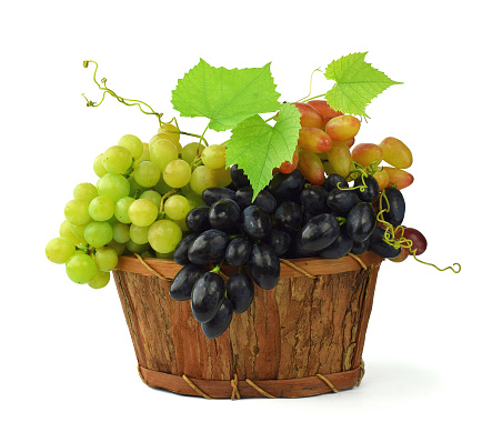 A variety of ripe grapes in a wooden basket. Isolated on white.