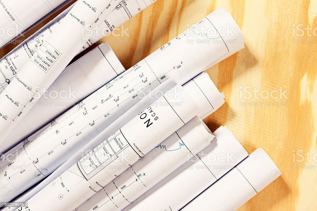Variety of rolled-up building plans on wooden surface royalty-free stock photo