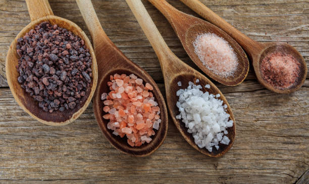 Variety of salts in spoons Variety of salts in wooden spoons salt stock pictures, royalty-free photos & images