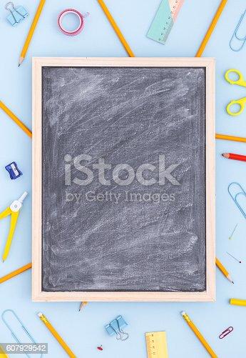 istock Variety of school supplies with blank blackboard. Vertical. 607929542