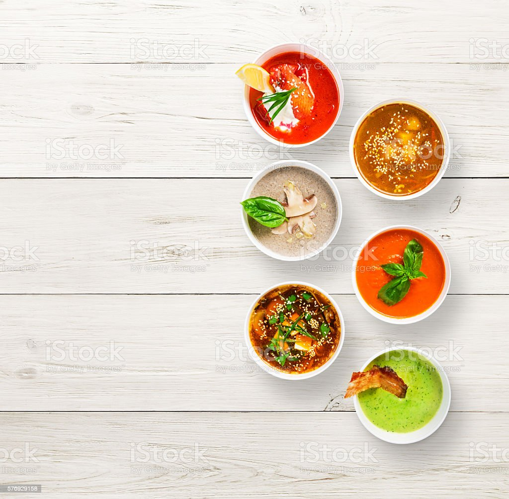 Variety of soups at white wood, top view, copy space stock photo