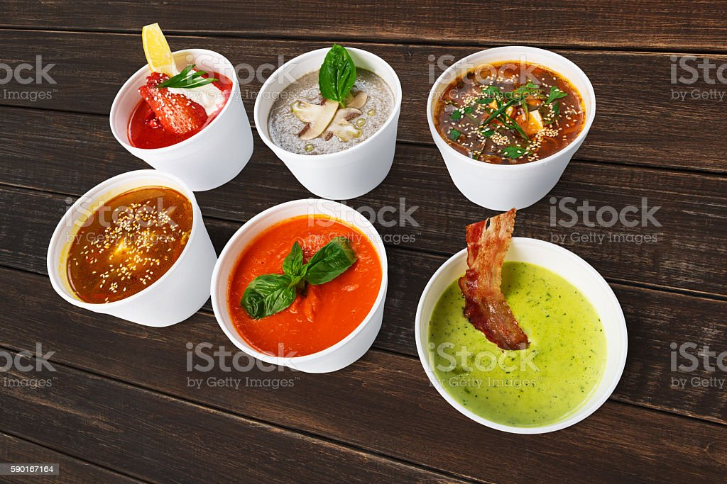 Variety of soups from different cuisines at brown wood stock photo