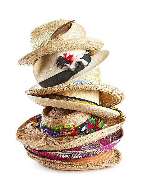Variety of straw hats stacked vertically Vertical stack of eight straw hats in a variety of shapes, textures, colors, and sizes, trimmed with ribbons, feathers, and raffia. Isolated on white background, vertical format. medium group of objects stock pictures, royalty-free photos & images