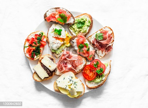 istock Variety of tapas sandwiches plate - sandwiches with prosciutto, avocado, salmon, egg, tomatoes, jamon, gorgonzola, brie, pear on a light background, top view. Delicious snack, appetizers. Copy space 1200642632