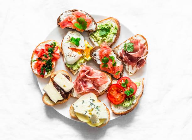 Vielzahl von Tapas Sandwiches Teller - Sandwiches mit Schinken, Avocado, Lachs, Ei, Tomaten, Jamon, Gorgonzola, Brie, Birne auf einem hellen Hintergrund, Ansicht von oben. Köstlicher Snack, Vorspeisen. Kopierraum – Foto