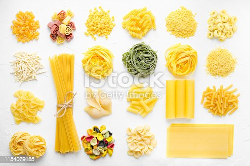 Variety of types and shapes of Italian pasta in rows on white background from above. Italian cuisine food concept and menu design. Dry pasta background texture. Top view. Flat lay.