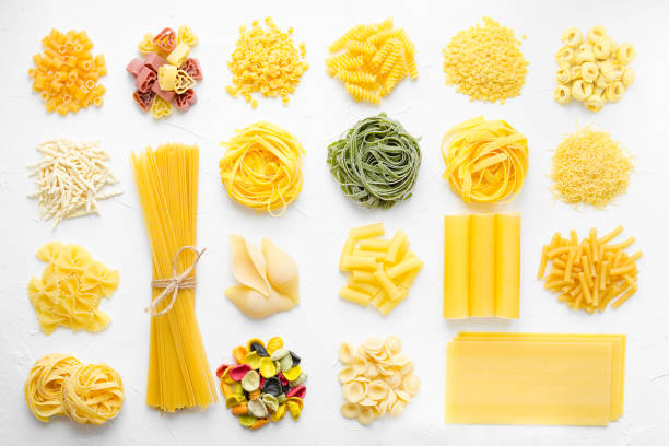 Variety of types and shapes of Italian pasta Variety of types and shapes of Italian pasta in rows on white background from above. Italian cuisine food concept and menu design. Dry pasta background texture. Top view. Flat lay. rigatoni stock pictures, royalty-free photos & images