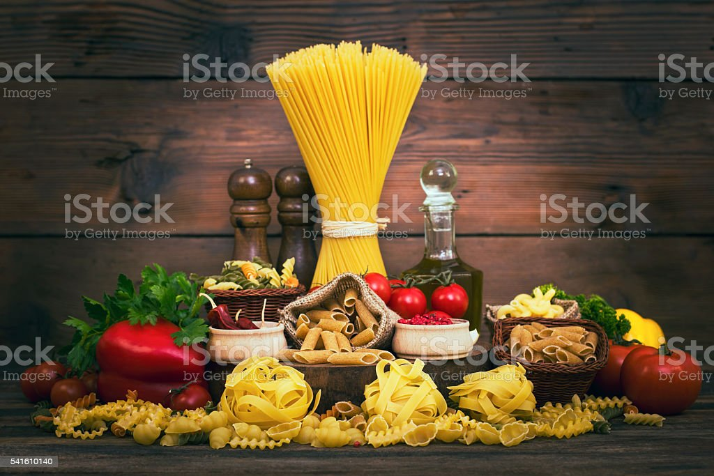 Variety of uncooked pasta and vegetables stock photo