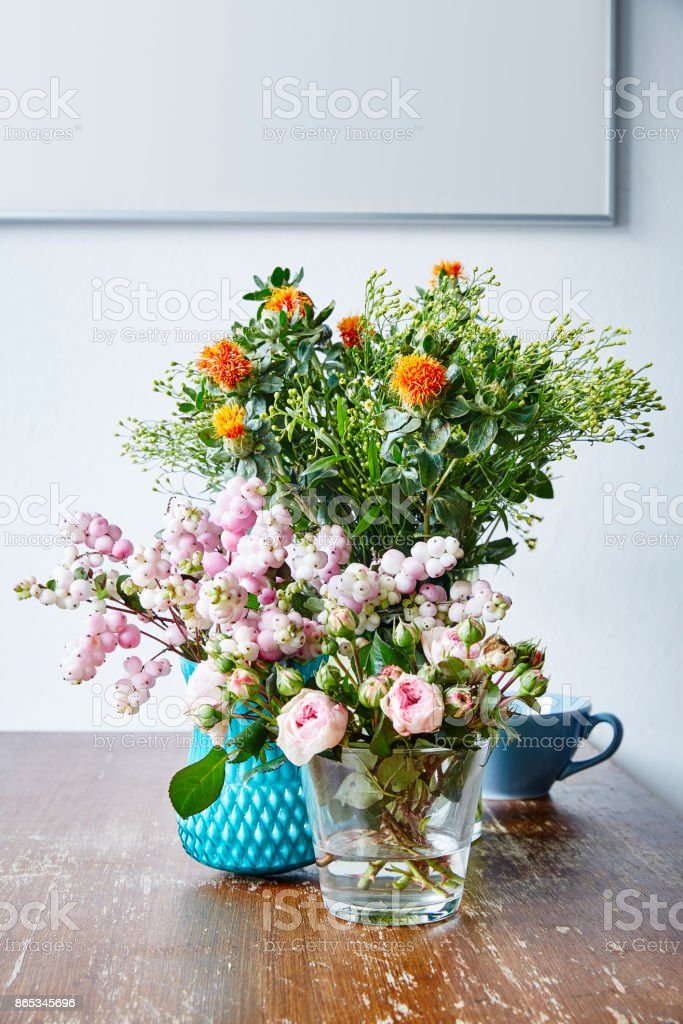 Variety Of Vases With Wild Flowers On Wooden Kitchen Table Stock