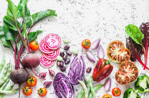 vielfalt an gemüse einen hellen hintergrund. rote beete, rotkohl, bohnen, tomaten, roten zwiebeln, paprika essen hintergrund. vegetarische kost-konzept - mangoldgemüse stock-fotos und bilder