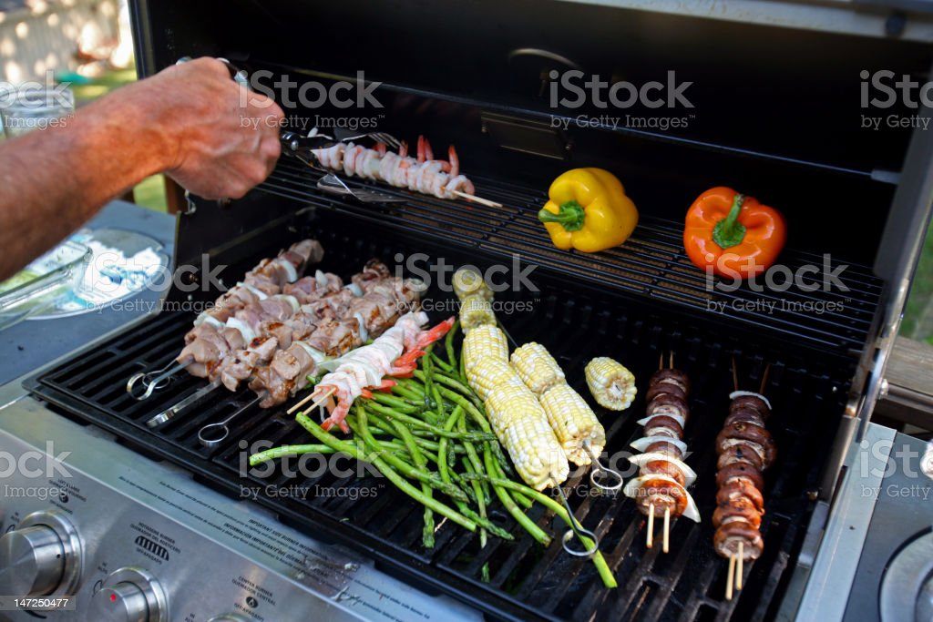 Variety of vegetables and meat kabobs on an open grill  stock photo