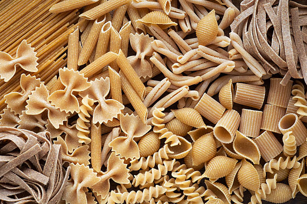 Variety of wholemeal pasta Variety of types and shapes of wholemeal pasta. Dry integral pasta background whole wheat stock pictures, royalty-free photos & images