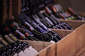 a lot of wine bottles put in crates for classified to display in a wine retail shop