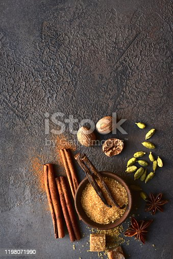 Variety of winter spices on a dark slate, stone or concrete background. Top view with copy space.