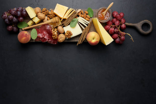 variety soft and hard cheeses, cold meat bresaola, nuts, grapes, peaches, jam on black background. cheese plate background - bresaola foto e immagini stock