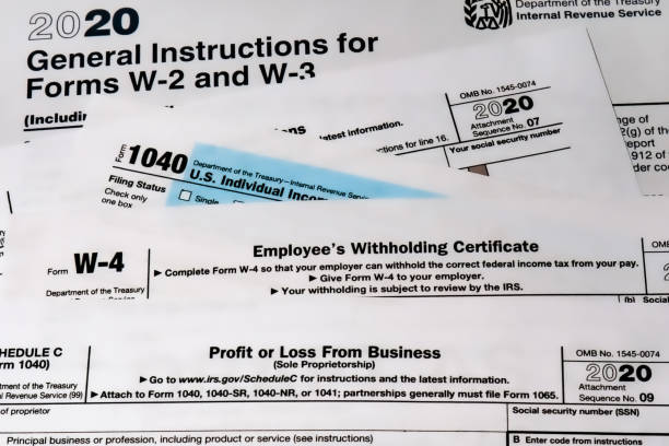 Various 2020 US IRS tax forms on a desktop. 2020 US tax forms lay on a desktop in West Des Moines, Iowa. 1040 tax form stock pictures, royalty-free photos & images