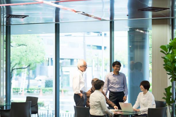 様々 な年齢のアジア事業チームがテーブルを囲んで会議します。 ストックフォト