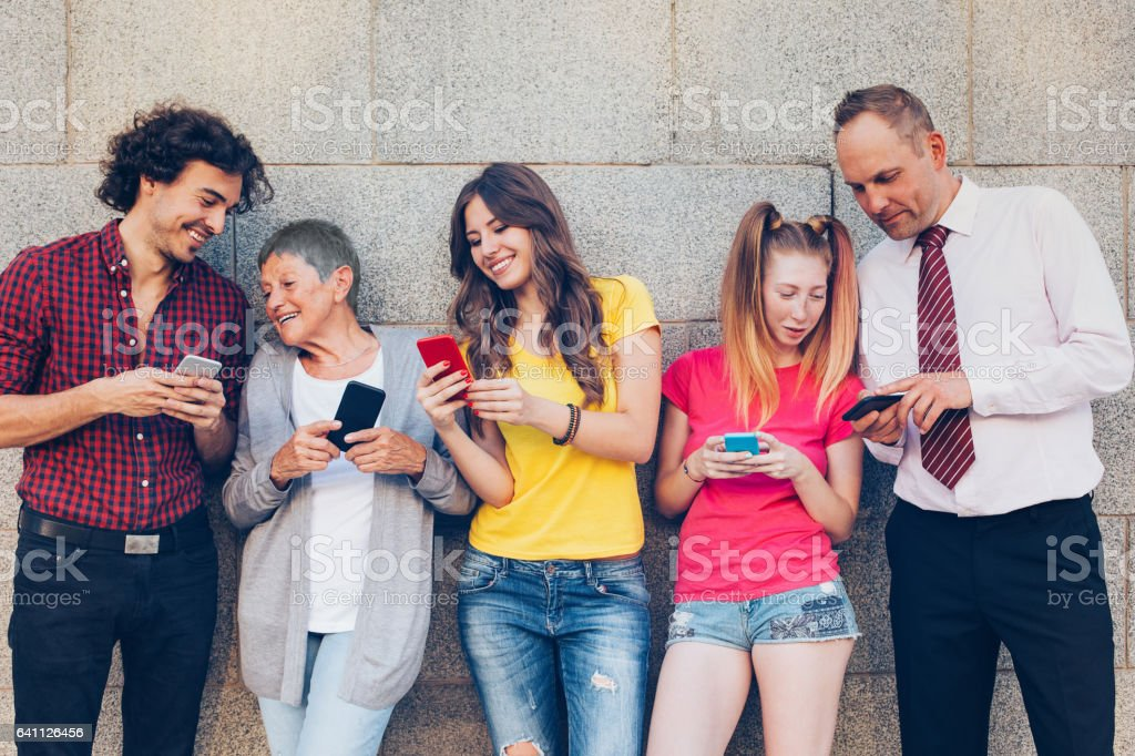 Various ages people texting and sharing outdoors stock photo