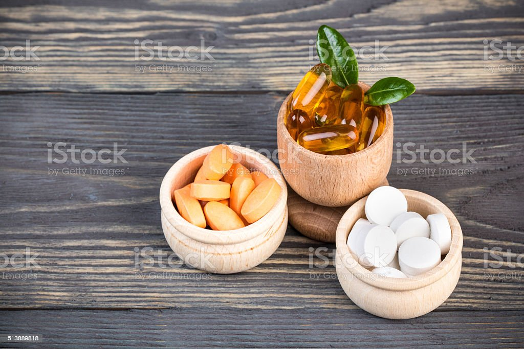 Various alternative and homeopatic pills in wooden containers stock photo