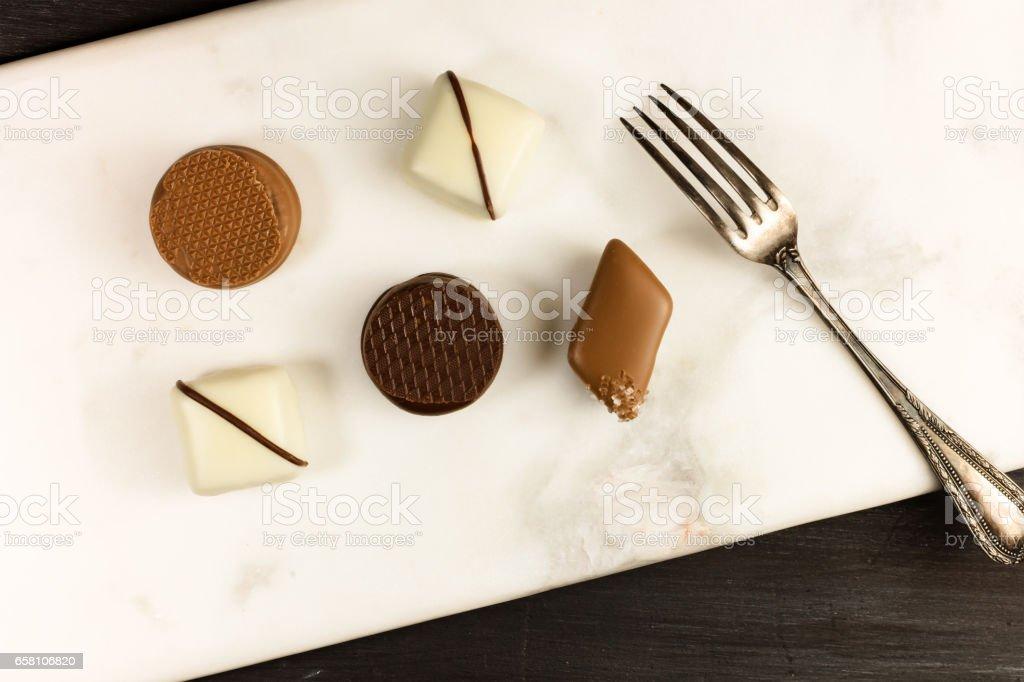 Various artisan chocolate bonbons with dessert fork royalty-free stock photo
