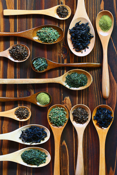 various assorted tea leaves in different shape wood spoons, overhead shot on wooden table - tea leaf stock photos and pictures