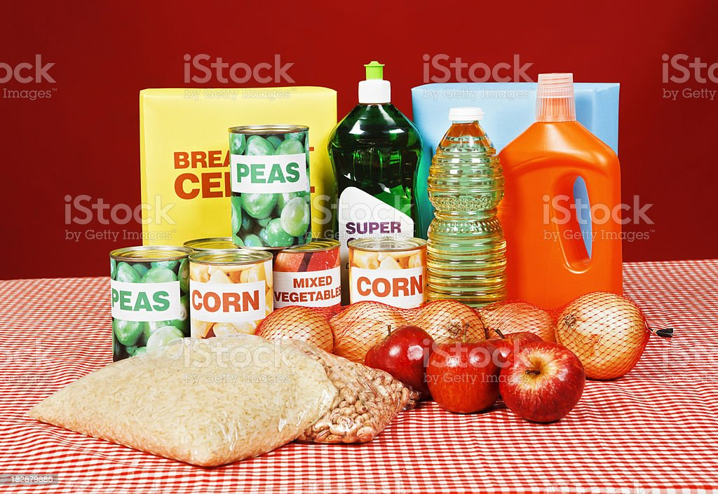 A selection of basic foods and cleaning products is grouped on a red...