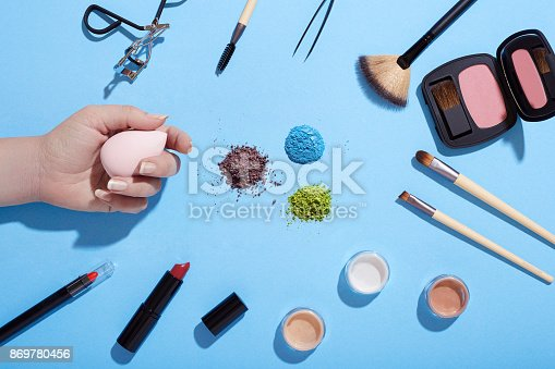 istock Various beauty products and crushed eye shadows on blue background 869780456