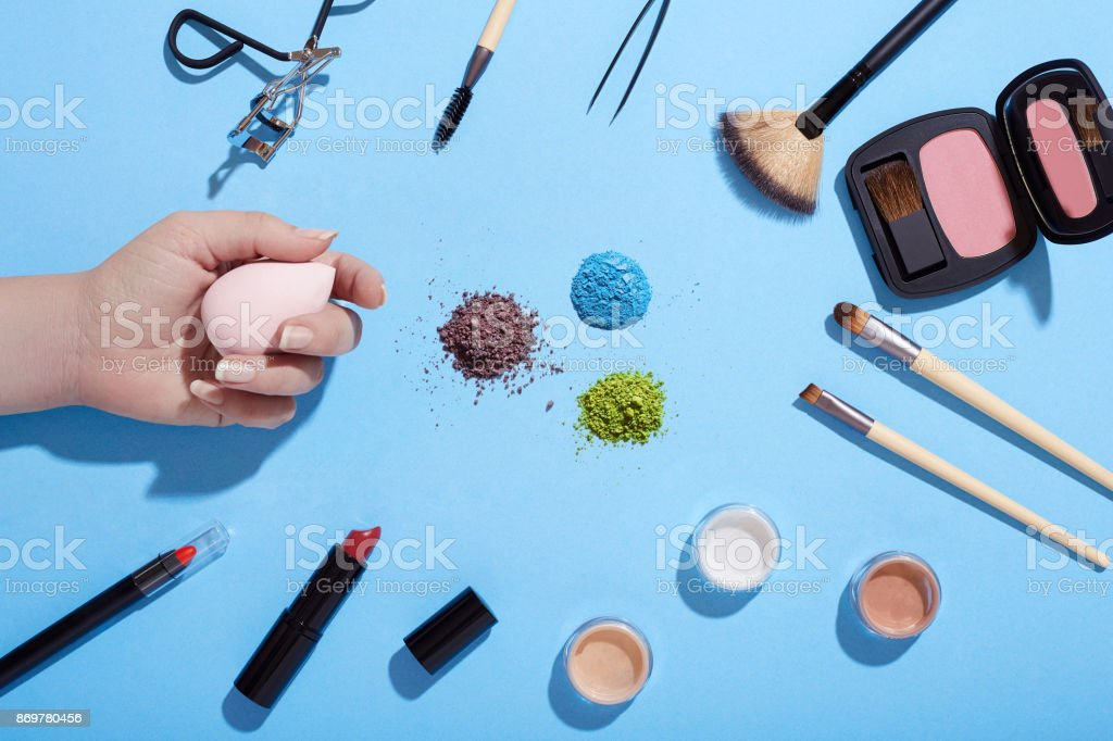 Various beauty products and crushed eye shadows on blue background stock photo