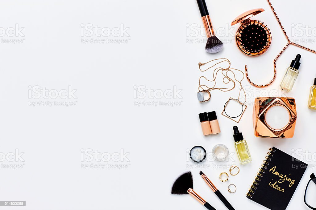 Various beauty products and jewelry against white background