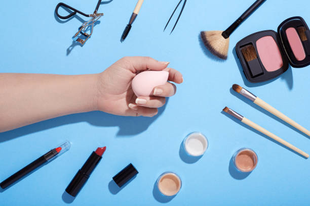 various beauty products on blue background - make up stock photos and pictures